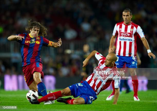 Carles Puyol of Barcelona is tackled by Marcos Landeira of Sporting de Gijon during the La Liga match between Barcelona and Sporting de Gijon at Nou...