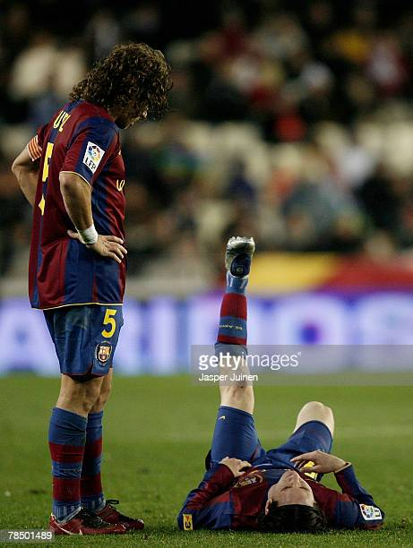 Carles Puyol of Barcelona looks at his injured teammate Lionel Messi laying on the pitch before abandoning the match during the La Liga match between...