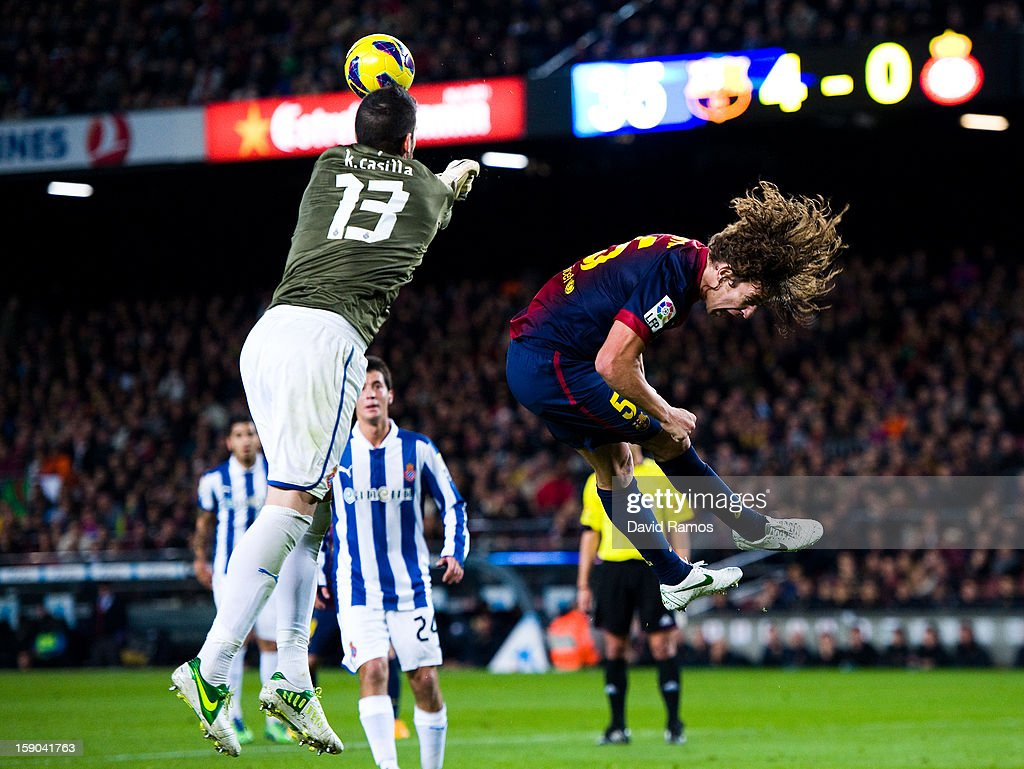 Carles Puyol of FC Barcelona duels for a high ball with Kiko Casilla of RCD Espanyol during the La Liga match between FC Barcelona and RCD Espanyol at Camp Nou on January 6, 2013 in Barcelona, Spain.