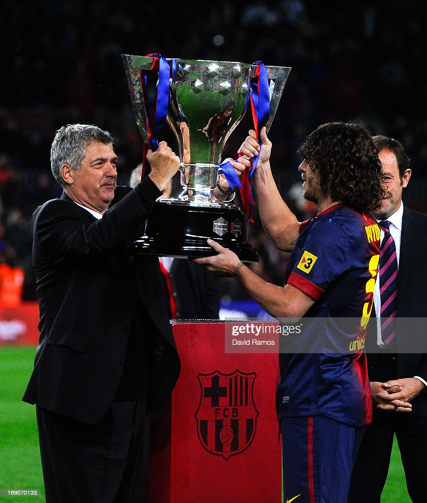 Carles Puyol of FC Barcelona receives the trophy from the President of the Spanish Football Federation, Antonio Maria Villa, during the celebration after winning the Spanish League after the La Liga match between FC Barcelona and Real Valladolid CF at Camp Nou on May 19, 2013 in Barcelona, Spain.