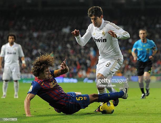Carles Puyol of FC Barcelona slides to stop Kaka of Real Madrid during the la Liga match between Real Madrid and Barcelona at Estadio Santiago...
