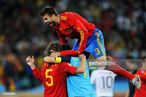 Carles Puyol of Spain celebrates with team mates Iker Casillas and Gerard Pique after victory and progress to the final during the 2010 FIFA World...