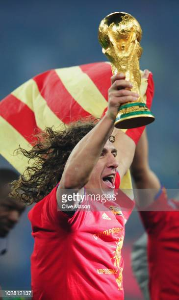Carles Puyol of Spain lifts the World Cup trophy as the Spain team celebrate victory following the 2010 FIFA World Cup South Africa Final match...