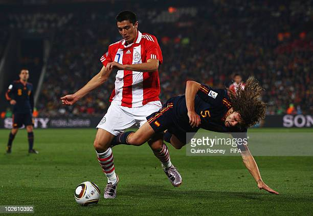 Carles Puyol of Spain tangles with Oscar Cardozo of Paraguay during the 2010 FIFA World Cup South Africa Quarter Final match between Paraguay and...