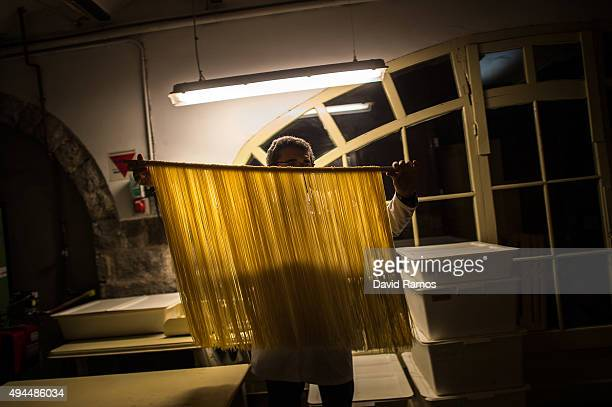 Carles Sanmarti takes fresh noodles ready to be dried in wood cabinets at Pasta Sanmarti factory on October 27 2015 in Caldes de Montbui Spain The...