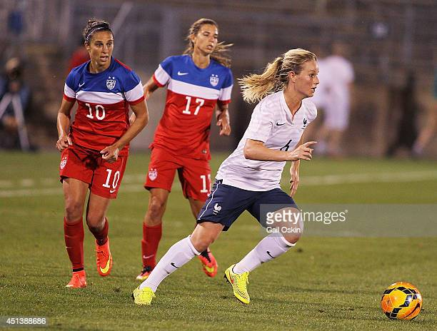 Carli Lloyd and Tobin Heath of the United States chase Amandine Henry of France down the field during a game between France and the United States...