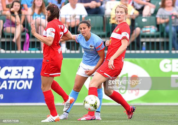 Carli Lloyd of the Houston Dash passes the ball between the defense of Brittany Taylor and Samantha Mewis of the Western New York Flash during the...
