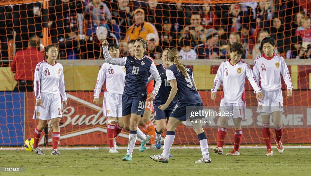 Carli Lloyd #10 of the United States celebrates her score with Heather O'Reilly #9 as dejected China team looks on in the second half at BBVA Compass Stadium on December 12, 2012 in Houston, Texas. USA won 4-0.