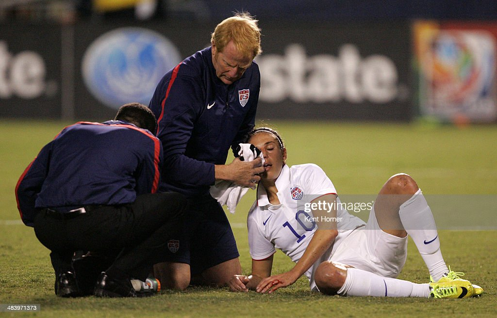 Carli Lloyd #10 of the United States is attended to by team trainers after getting a bloody nose in the first half of the game against China during an international firendly match at Qualcomm Stadium on April 10, 2014 in San Diego, California.