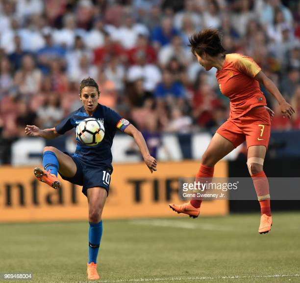 Carli Lloyd of the United States kicks the ball past defender Wang Shuang of China in the second half of an international friendly soccer match at...