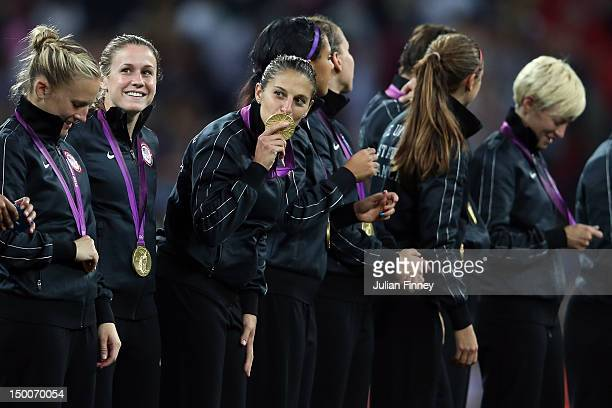 Carli Lloyd of the United States kisses her gold medal as Heather O'Reilly looks on after defeating Japan by a score of 21 to win the Women's...