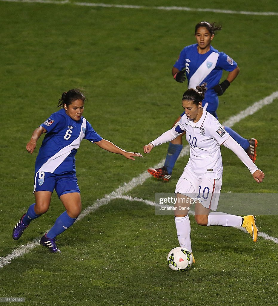 Carli Lloyd #10 of the United States moves between Gloria Aguilar #6 and Londy Barrios #5 of Guatemala during the 2014 CONCACAF Women's Championship at Toyota Park on October 17, 2014 in Bridgeview, Illinois. The United States defeated Guatemala 5-0.