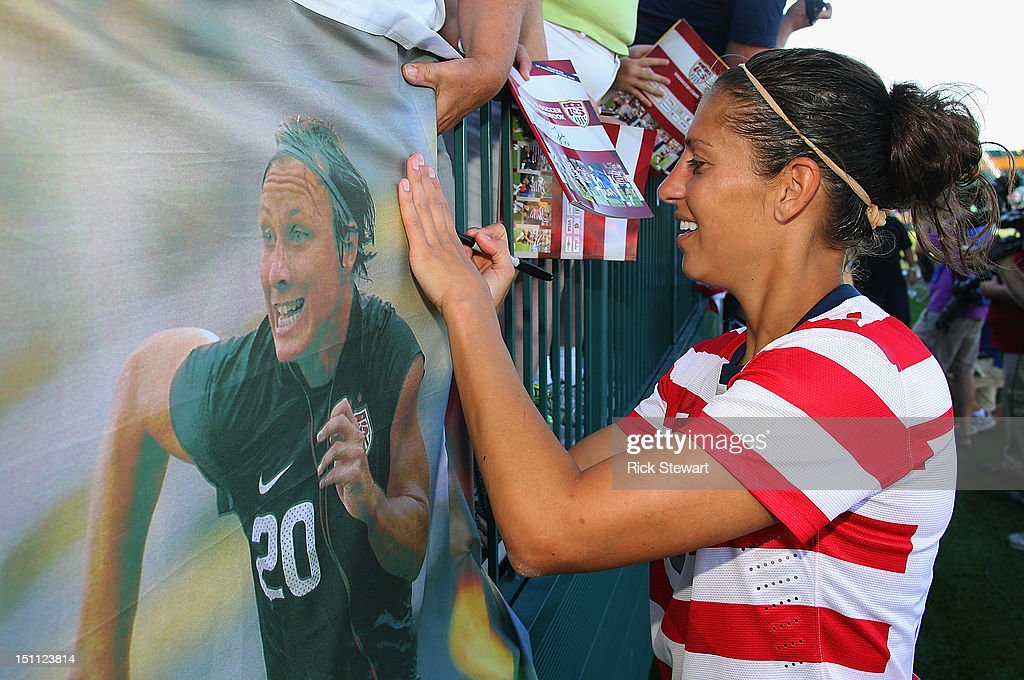 Carli Lloyd #10 of the United States Womens National Team signs a poster of Abby Wambach for a fan after playing Costa Rica during their friendly match at Sahlen's Stadium on September 1, 2012 in Rochester, New York. The US won 8-0.