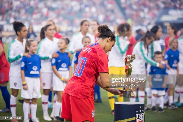 Carli Lloyd of United States of the U.S. Women's 2019 FIFA World Cup Championship team places the FIFA World Cup trophy on the pedestal during the...