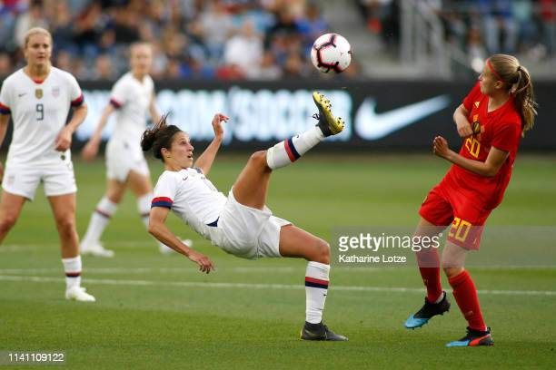 Carli Lloyd of United States Women's National Team kicks the ball away from Julie Biesmans of Belgian Women's National Team during the first half of...