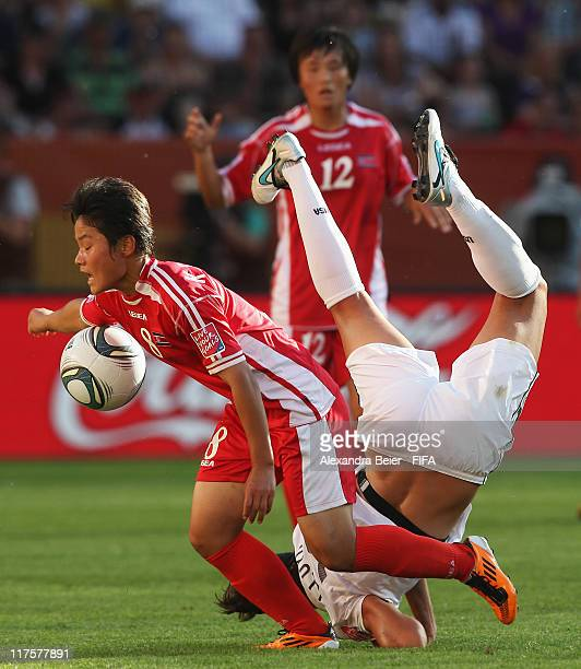 Carli Lloyd of USA falls after fighting for the ball with Kim Su Gyong of Korea DPR during the FIFA Women's World Cup 2011 Group C match on June 28...