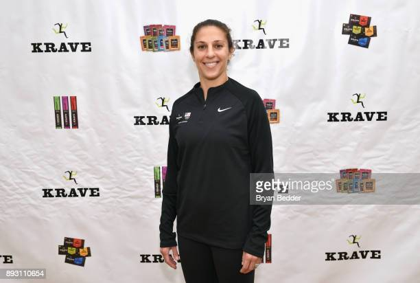 Carli takes a photo in front of the KRAVE banner at Asphalt Green on December 13 2017 in New York City