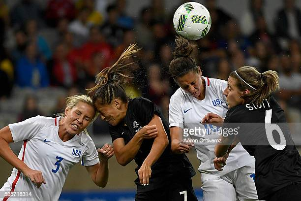 Carlie Lloyd of the United States heads in a 10 goal as she and teammate Allie Long go head to head with Alie Riley of New Zealand and Rebekah Stott...