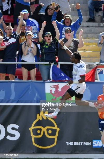 Carlin Isles of the United States leaps in the air as he celebrates scoring a try late in a match against New Zealand during the USA Sevens Rugby...