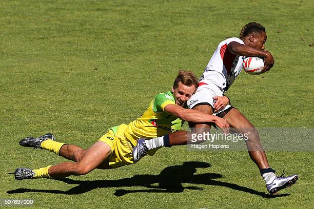 Carlin Isles of USA is tackled by John Porch of Australia during the 2016 Wellington Sevens plate semi-final match between Australia and USA at...