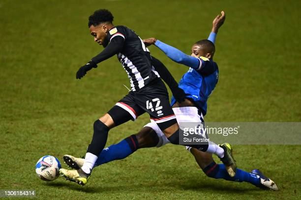Carlisle defender Aaron Hayden slides in to challenge Grimsby forward Julien Lamy during the Sky Bet League Two match between Carlisle United and...