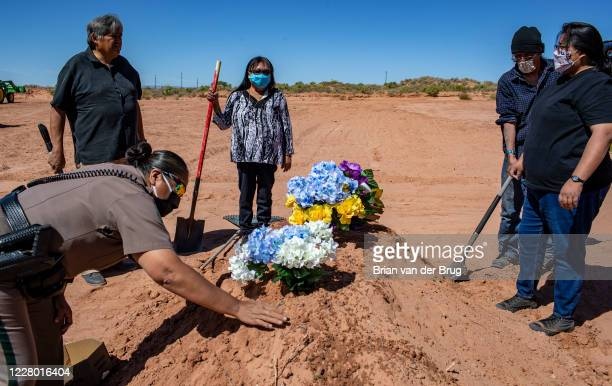 Carlita Bergen, center, holds a shovel as Navajo Nation police officer Carolyn Tallsalt smooths dirt over COVID-19 victim Arnold Billy's grave while...