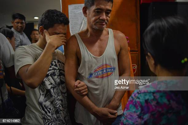 Carlito Garcia and his son Chester Garcia both alleged drug suspects detained at a small secret cell behind a wooden cabinet being interviewed by a...