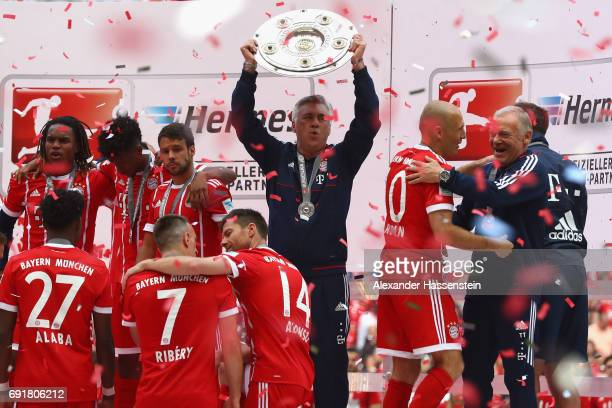 Carlo Ancelotti head coach of Bayern Muenchen poses with the Championship trophy in celebration of the 67th German Championship title following the...