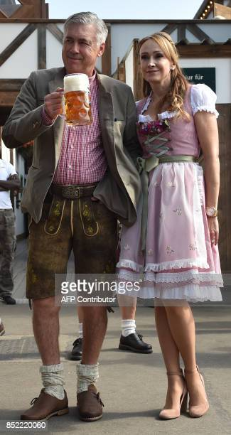 Carlo Ancelotti Italian head coach of German first division Bundesliga football club FC Bayern Munich holds a beer mug as he poses with his wife...