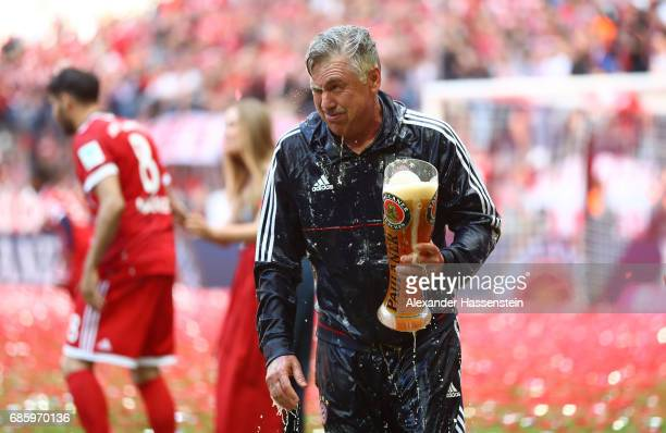 Carlo Ancelotti Manager of Bayern Muenchen is showered in beer by his players following the Bundesliga match between Bayern Muenchen and SC Freiburg...