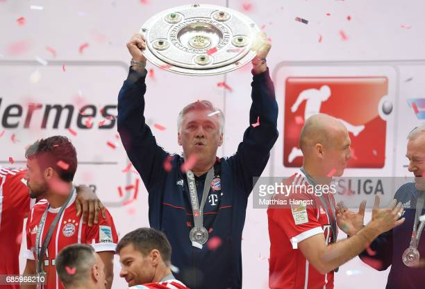 Carlo Ancelotti Manager of Bayern Muenchen poses with the Championship trophy in celebration of the 67th German Championship title following the...