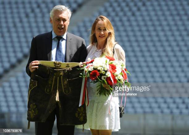 Carlo Ancelotti new head coach of German Bundesliga soccer club FCBayern Munich poses with a pair of leather trousers next to his wife Mariann...