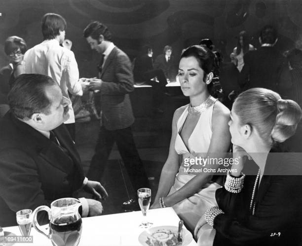 Carlo Caprioli talking to Juliette Mayniel and Beba Loncar at nightclub in a scene from the film 'Listen Let's Make Love' 1968