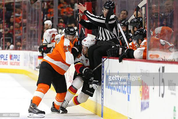 Carlo Colaiacovo of the Philadelphia Flyers hits Josh Jooris of the Calgary Flames as linesmen Scott Driscoll goes over the boards in the first...