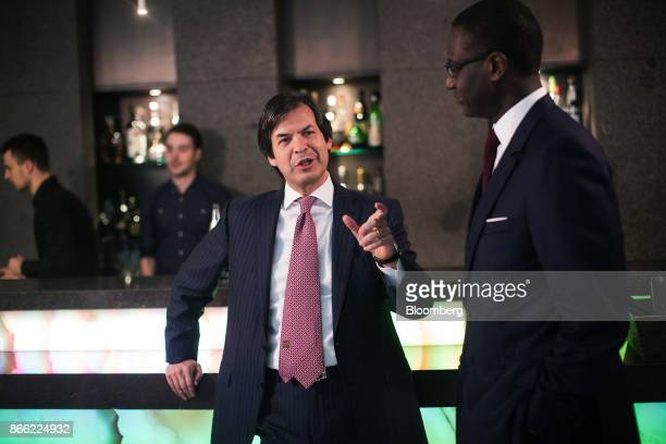 Carlo Messina chief executive officer of Intesa Sanpaolo SpA center gestures as he speaks with Tidjane Thiam chief executive officer of Prudential...