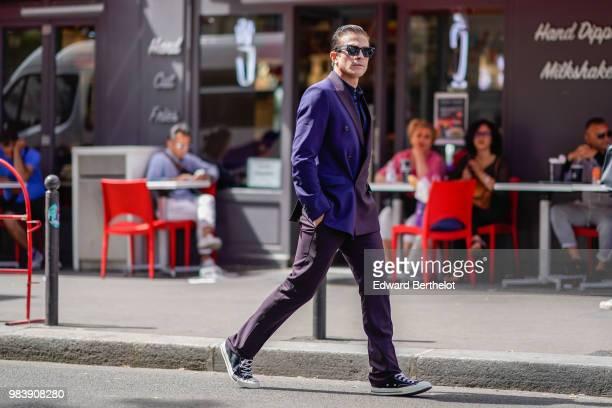 Carlo Sestini wears a purple blazer jacket, sunglasses, black pants, sneakers shoes, outside Paul Smith, during Paris Fashion Week - Menswear...