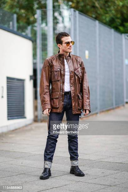 Carlo Sestini wears sunglasses a brown leather jacket a white top denim pants during London Fashion Week Men's June 2019 on June 09 2019 in London...