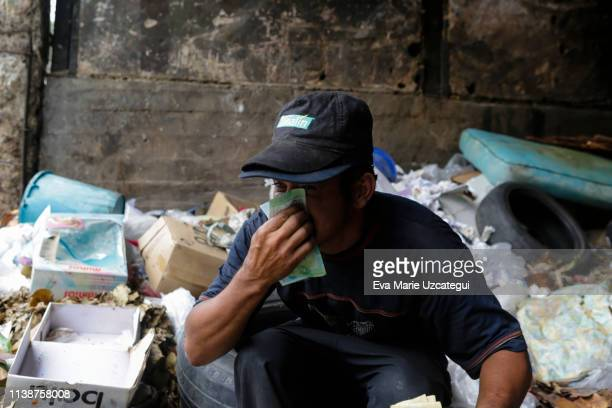 Carlos 30 years old blows his nose with Venezuelan Bolivar bank notes in a garbage dump in Petare on April 10 2019 in Caracas Venezuela Political and...