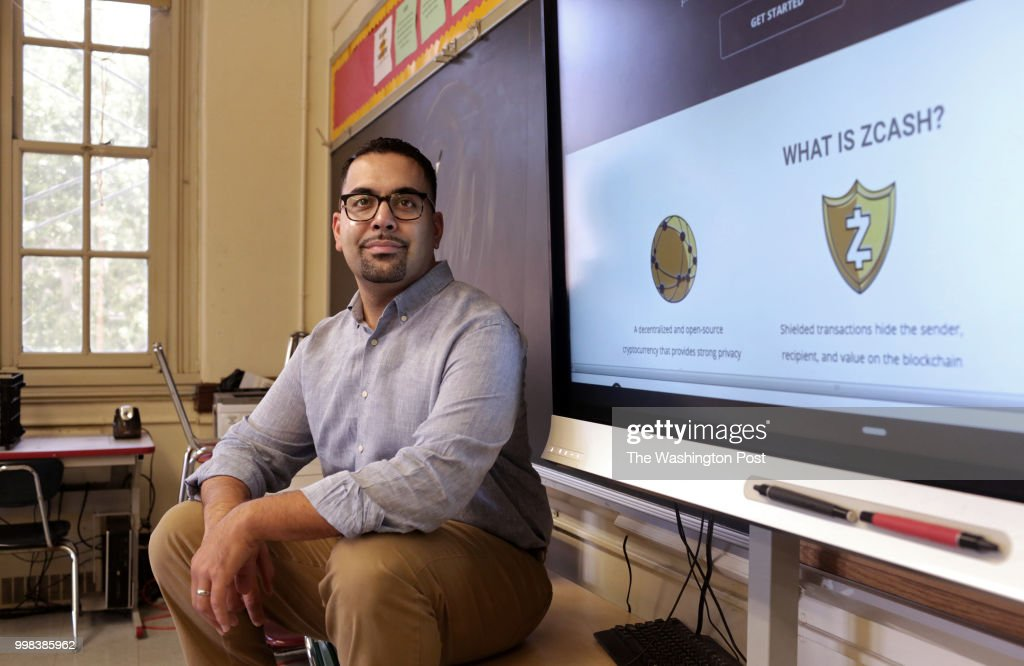 Carlos Acevedo, a senior English teacher and technology coordinator at the Morris Academy for Collaborative Studies, poses for a portrait next to a presentation on the internet currency Zcash, in the Bronx school in New York, on July 11, 2018.