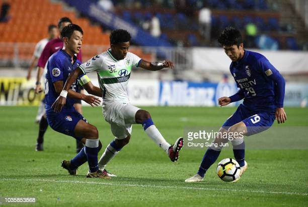 Carlos Adriano of Jeonbuk Hyundai Motors competes for the ball with Han EuigoWon of Suwon Samsung Bluewings during the AFC Champions League Quarter...