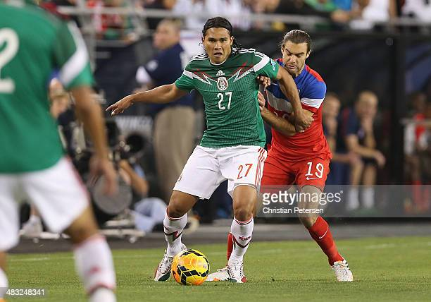 Carlos Alberto Pena of Mexico controls the ball ahead of Graham Zusi of USA during the International Friendly at University of Phoenix Stadium on...