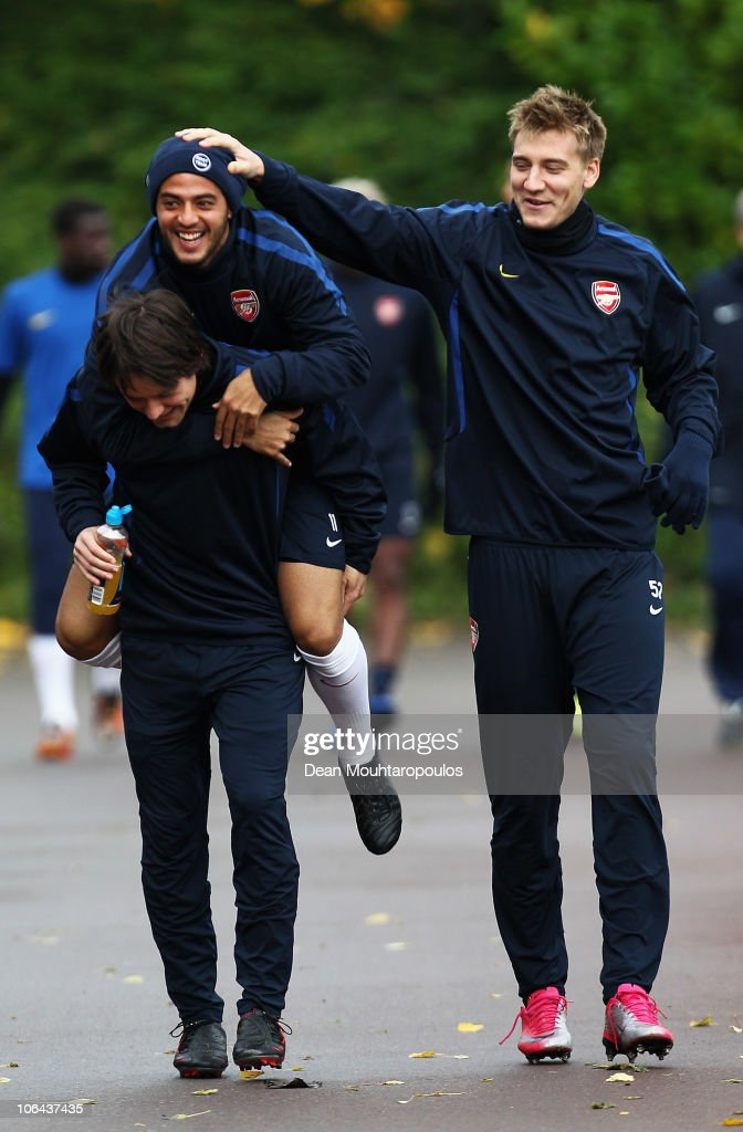 Carlos Alberto Vela jumps on the back of team mate Tomas Rosicky as Nicklas Bendtner (R) laughs during a training session ahead of the UEFA Champions League Group H match against Shakhtar Donetsk at the club's complex at London Colney on November 2, 2010 in St Albans, England.
