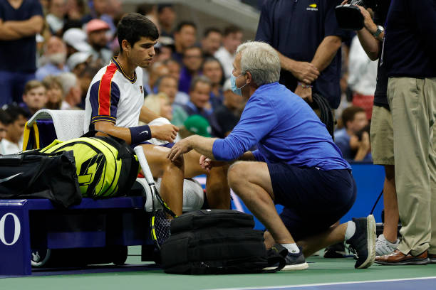 Carlos Alcaraz of Spain talks with a trainer during his Men's Singles quarterfinals match against Felix Auger-Aliassime of Canada during on Day Nine...