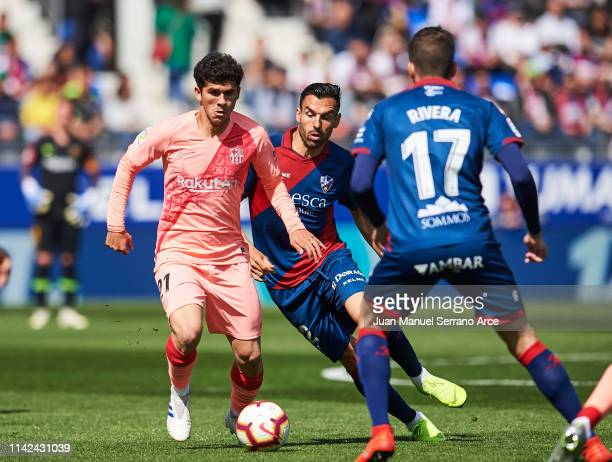 Carlos Alena of FC Barcelona duels for the ball with Enrique Gallego of SD Huesca during the La Liga match between SD Huesca and FC Barcelona at...
