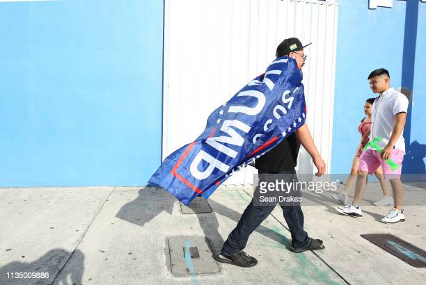 Carlos Arias of Honduras is draped in a Trump 2020 banner and a replica of the national flag of Honduras during the annual Calle Ocho Festival in the...