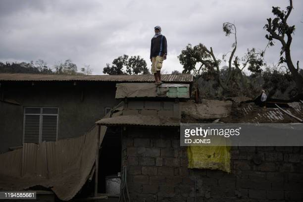 Carlos Armando poses for a portrait as he works to clear volcanic ash from the eruption of the Taal volcano from the roof of his house in Buso Buso...