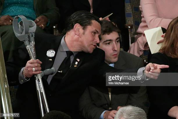 Carlos Arredondo and Jeff Bauman who was injured during the Boston bombing wait for US President Barack Obama to deliver the State of the Union...
