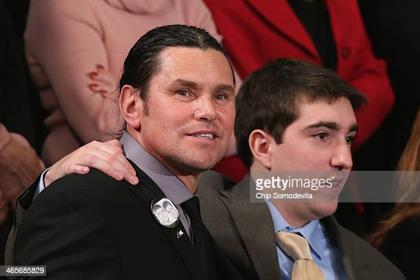 Carlos Arredondo and Jeff Bauman who was injured during the Boston bombing watch as US President Barack Obama delivesr the State of the Union address...