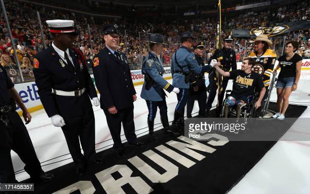 Carlos Arredondo , the man who came to his aid immediately following the explosions, wheels out Boston Marathon bombing victim, Jeff Bauman , to wave...