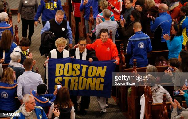 Carlos Arredondo walks down the aisle carrying a Boston Strong flag during a special The Blessing of the Athletes service at the Old South Church on...